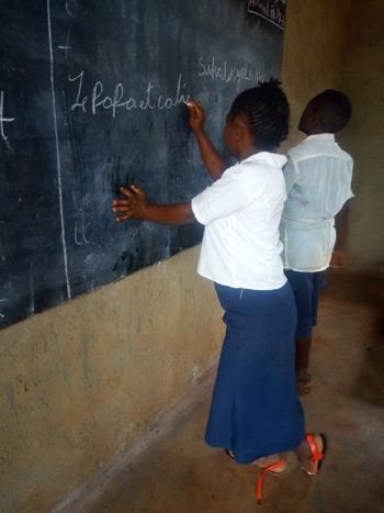 Elèves du centre de rattrapage scolaire de Mangina écrivant au tableau noir