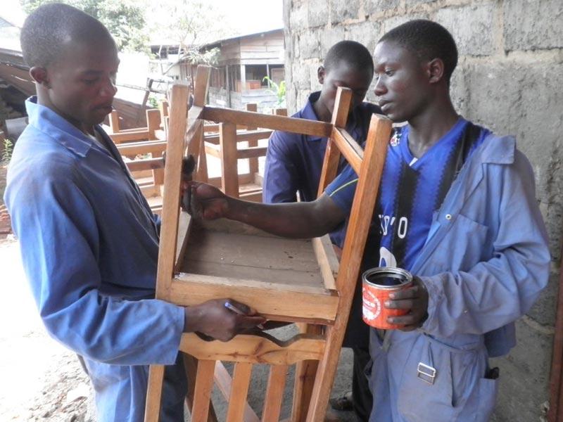 Apprentis menuisiers de Goma vernissant une chaise