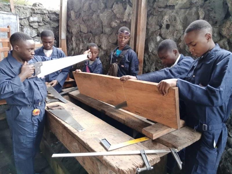 Apprentissage du maniement de la scie pour les enfants soldats démobilisés apprentis menuisiers de Goma