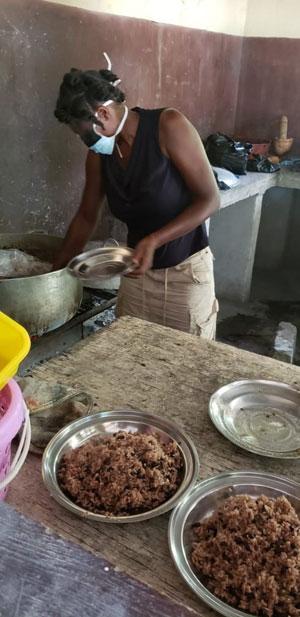 Cuisinière de l'école St Alphonse en Haïti préparant le repas de cantine pour les enfants en période de confinement