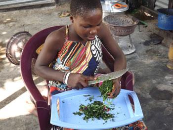 Préparation du repas de midi par une fillette du centre Ndako Ya Biso pour l'accueil des enfants des rues à Kinshasa