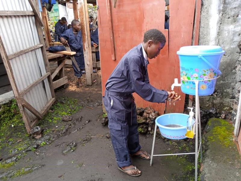 Lavage des mains à l'entrée du centre de formation en menuiserie Aprojed à Goma pour lutter contre la propagation du virus Covid-19.