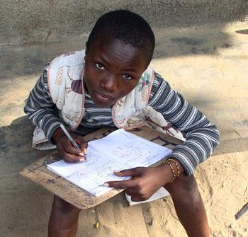 un enfant des rues en séance d'alphabétisation dans la rue à Kinshasa