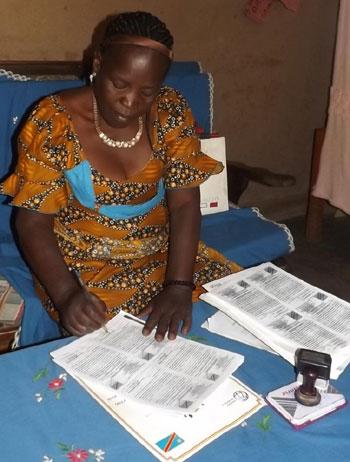 Signature des certificats d'indigence par Madame Kamuswekere Neema, Chef du bureau des Affaires Sociales et Solidarité Nationale du Territoire de Lubero