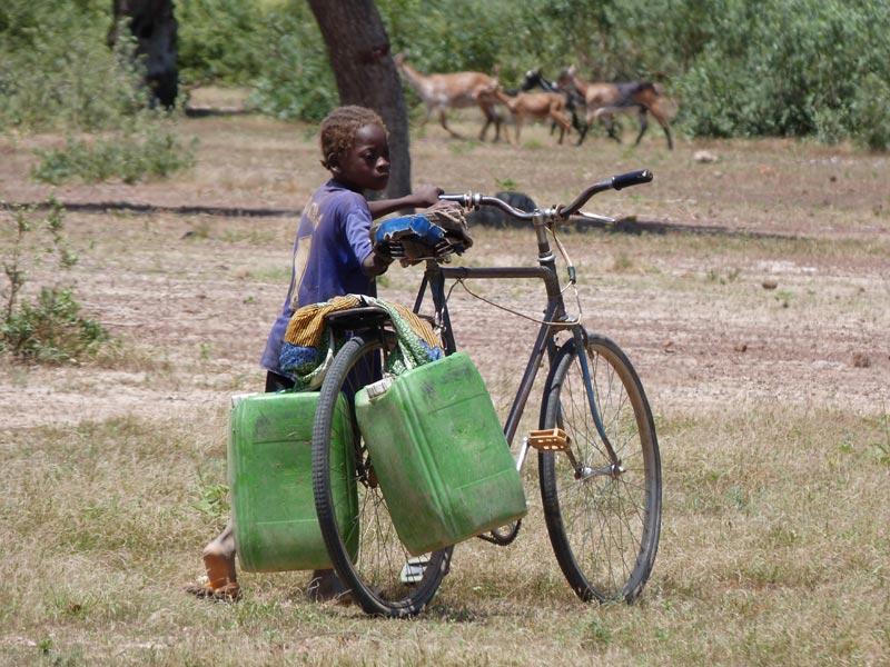 Enfant du Burkina Faso poussant son vélo plus grand que lui