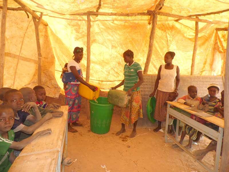 Les mamans apportent l'eau pour leurs enfants à l'école de Koulmastanga au Burkina Faso