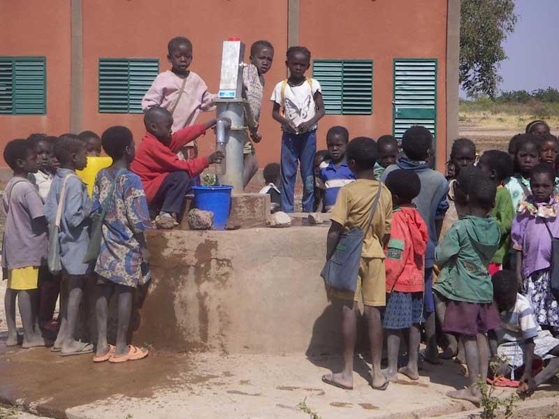 Les enfants puisent de l'eau au forage devant l'école de Guiè au Burkina Faso.