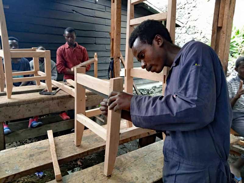 Apprenti menuisier de Goma apprenant à monter une chaise par assemblage tenon-mortaise.