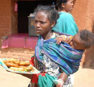 Petite vendeuse de beignets dans les rues d'Ambatolampy à Madagascar