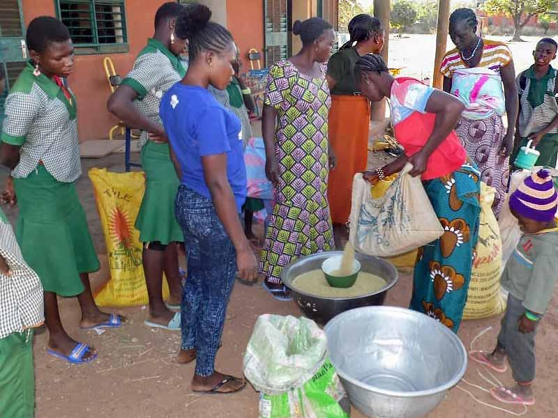 Au Burkina Faso, les mamans apportent des céréales pour alimenter la cantine endogène de l'école Kelyam à Guiè