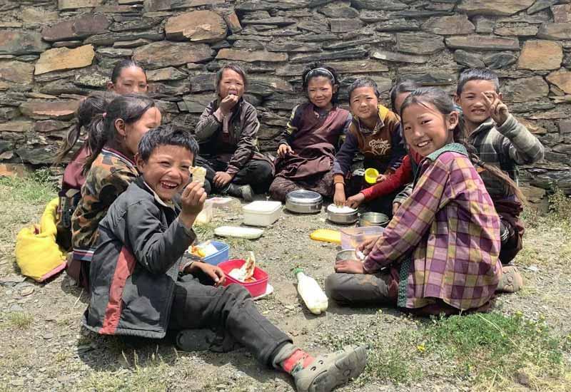 Au Népal, les élèves de la Siddartha Kula Mountain School au Dolpo prennent leur repas de midi à même le sol.