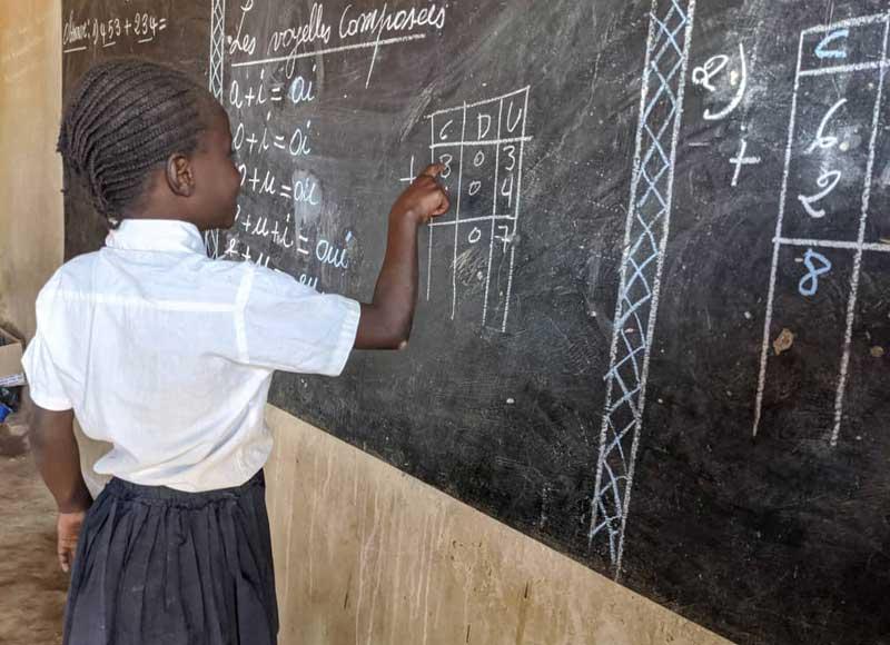 Elève de l'école Bumi à Karavia au tableau noir pendant un cours de soutien scolaire.