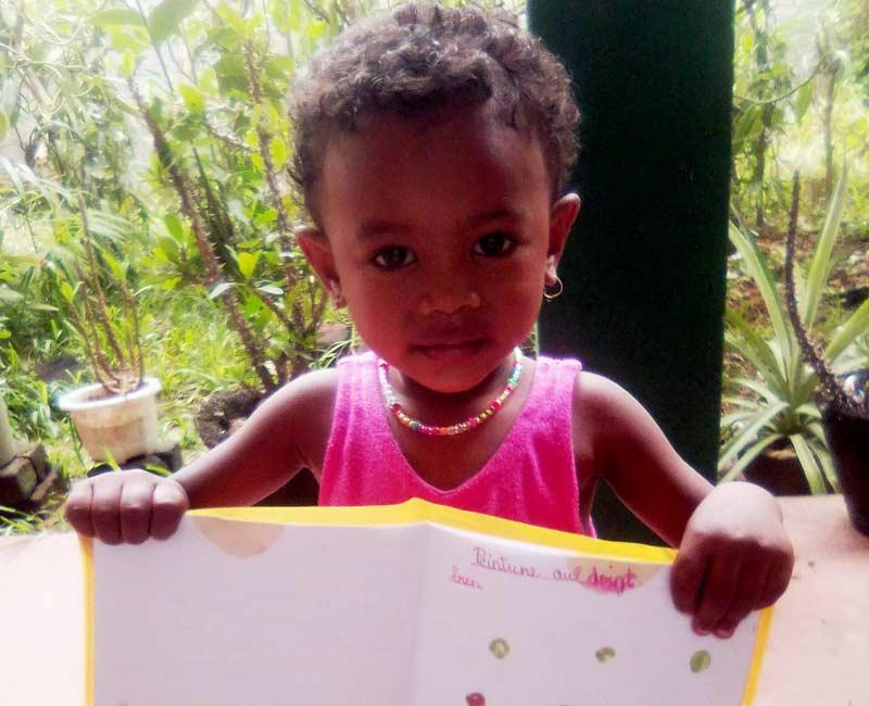 Sania montre avec fierté son cahier d'écolière