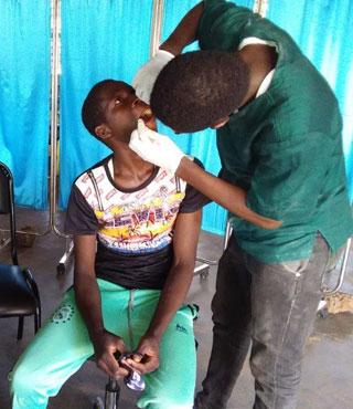 Examen bucco-dentaire pratiqué par un étudiant sur une élève de l'école de Guiè au Burkina Faso