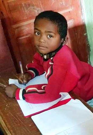 Ecolier de Madagascar écrivant en classe dans son cahier