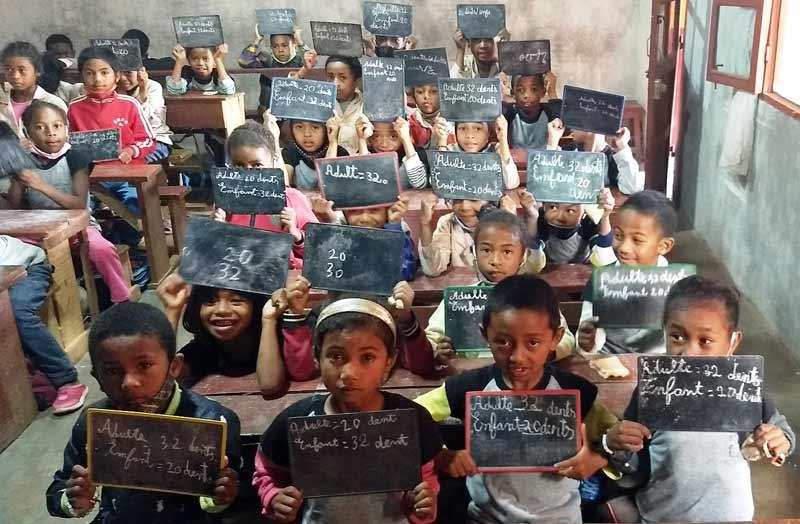 Apprentissage de l'écriture et du calcul sur une ardoise pour les élèves du Centre Akany Aina à Madagascar